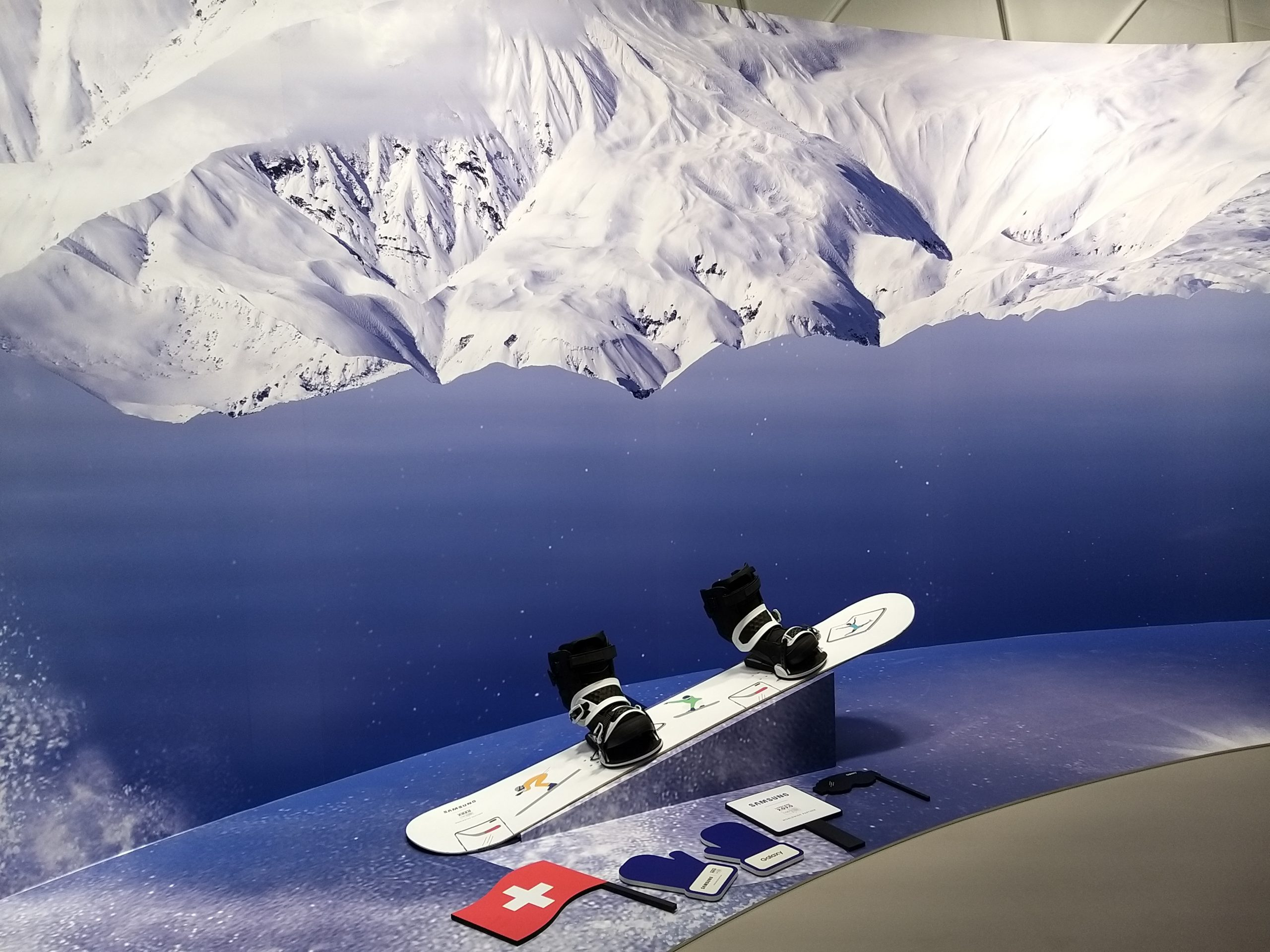 Picture of snowboard with Swiss flag and mountain in background.